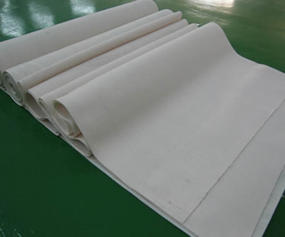There are several rolls of woven filter cloths piled with each other.